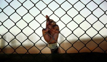 An Iraqi detainee holds onto a fence enclosing him at the Camp Cropper detention centre, located in Baghdad, on May 21, 2008.  There are approximately 22,000 detainees being held by US forces in two detention facilities in Iraq, up from only about 14,000 before the American troop surge this year.  Camp Cropper currently holds approximately 3,000 detainees. The detainee population contains, juveniles, insurgents of all anti-coalition groups in Iraq, and innocent Iraqis detained during military operations.  Military officials have initiated programs for the detainees in the detention facility including educational classes, Islamic discussion courses, work programs, art classes and a vigorous review board to discuss with detainees the circumstances surrounding their arrest.  AFP PHOTO/DAVID FURST
